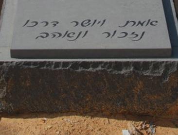 כיתוב שחור בכתב מעוגל המנציח את הנפטר