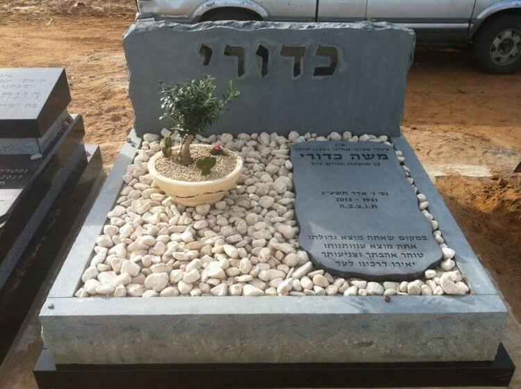 מצבות בצפון מאבן חברון כהה וחצץ בשילוב פרחים