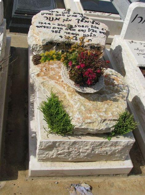 מצבה בחיפה מעוטרת בפרחים מאבן ירושלמית