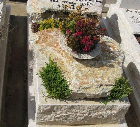 קישוט של צמחייה ופרחים על מצבת סלעים טבעית
