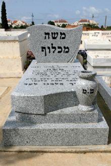 מצבת אבן גרניט לבנה עם כיתוב שחור ומשטח מוגבהה וכד מעוצב מעל המצבה